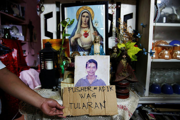 A relative holds a cardboard sign next to a picture of Florjohn Cruz inside the house where he was killed in a police drugs buy-bust operation in Manila