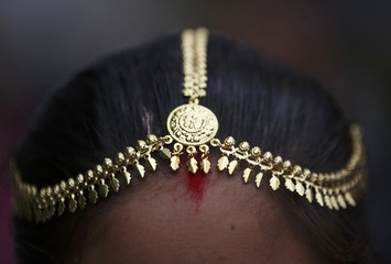 A traditional ornament is pictured on the head of a Tharu girl during a parade marking an Elephant Festival event at Sauraha in Chitwan