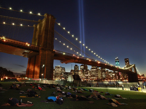 People take part in a sunset yoga session as the Tribute in Light shines over the Brooklyn Bridge on the East River on the 11-year anniversary of the 9/11 attacks in New York