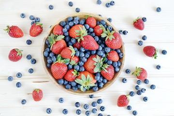 Fresh organic berry fruits, wooden plate