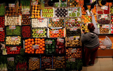 A woman makes purchases in a fruits and vegetables shop at a food market in the Andalusian capital of Seville
