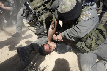 Israeli border police detain a Palestinian protester at a construction site for the controversial Israeli barrier in al Wallaje