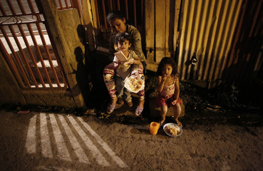 A woman with her two children eat food in Triangulo de la Solidaridad, a low-income neighbourhood, north of San Jose