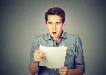 Shocked man holding some documents