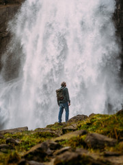 Man on background of waterfall