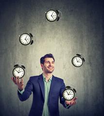 business man juggling his time alarm clocks