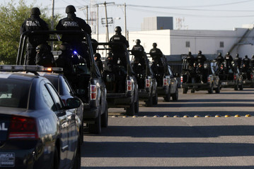 Members of Mexico's Federal Police ride on their vehicles during a presentation to the media in Ciudad Juarez