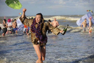 A man runs with a kite at the beach while holding a bottle of champagne during the traditional New Year's swim in Malo-les-Bains