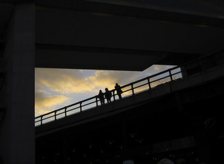 People stand on the High Line park under the Standard Hotel as the sun sets behind them in New York