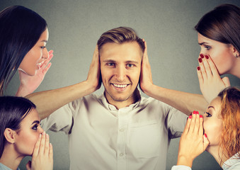 Four women whispering gossip to a man who covers ears ignoring all surrounding noise