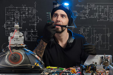 the man is engaged in repair of electronics
