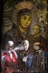 Visitors are reflected in a picture hanging in the Church of the Nativity, ahead of Christmas in Bethlehem