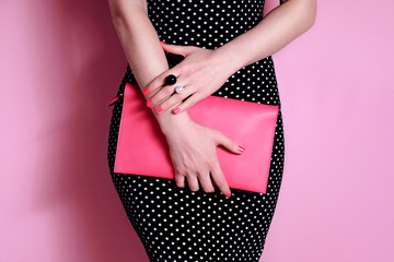 Close up shapely woman in evening black dress with pink bag