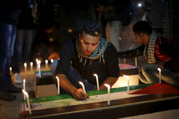 Palestinian places a candle on a symbolic coffin during a rally to pay tribute to Palestinians who organizers said were killed recently by Israeli troops, on Christmas day in Gaza City