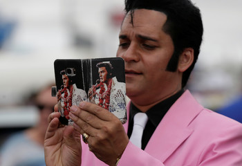 Elvis Presley tribute artist Stuart Vieyra takes a picture with his camera phone during a street parade at the 25th annual Parkes Elvis Festival in the rural Australian town of Parkes, west of Sydney