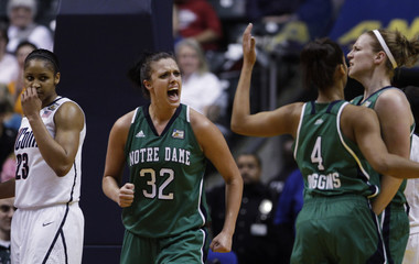 Fighting Irish Bruszewski celebrates with teammates as Huskies Moore looks on during their semi-final NCAA women's Final Four college basketball game in Indianapolis