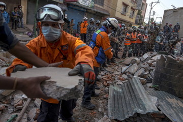 Nepalese military personnel remove debris in search of survivors after a fresh 7.3 earthquake struck, in Kathmandu