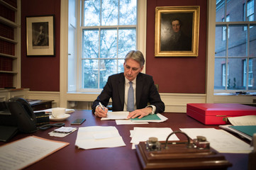 Britain's Chancellor of the Exchequer Philip Hammond reads through his Autumn Statement as he poses for a photograph in his office in 11 Downing Street, London