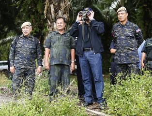 Malaysia's Home Minister Hishammuddin Hussein looks through binoculars as he visits the area near the location where armed men are holding off, in Sahabat 17 plantation farm, outside Lahad Datu on Borneo island