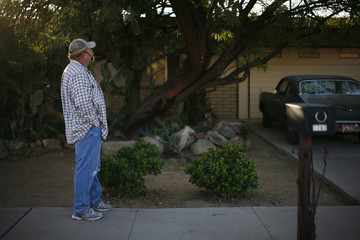 A man stands outside the home of accused gunman Jared Lee Loughner in Tucson
