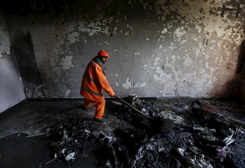 A municipal worker removes debris from a house after a Taliban attack in Kabul
