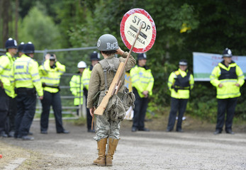 Protestor Rory Rush poses in front of police officers protecting the entrance gate of a site run by Cuadrilla Resources outside the village of Balcombe in southern England
