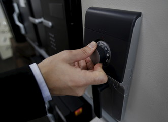 A staff turns a dial for a safety deposit box's combination lock during a photo opportunity at a security showroom in Tokyo