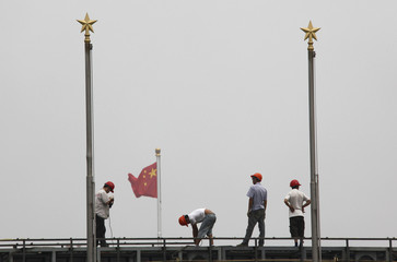 Workers stand atop scaffolding in front of the Chinese national flag on Tiananmen Square on a hot and hazy day in Beijing