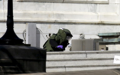 A police bomb squad officer kneels down to closely inspect a suspicious package on the U.S. Capitol grounds in Washington