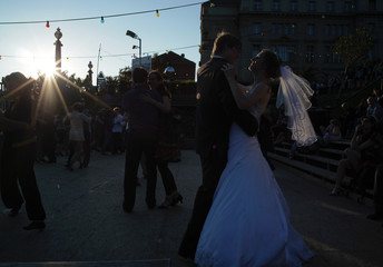 A couple who just got married pose for their wedding pictures as tango enthusiasts dance the tango at a beach bar near the river Spree in Berlin