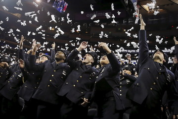 Newly inducted New York Police members throw their ceremonial white gloves in the air as they take part in a graduation ceremony at Madison Square Garden in the Manhattan borough of New York