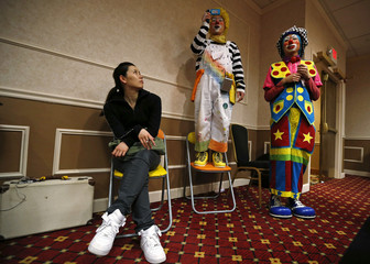 Mikae Iwana looks at clowns as they watch performances at the World Clown Association's annual convention in Northbrook