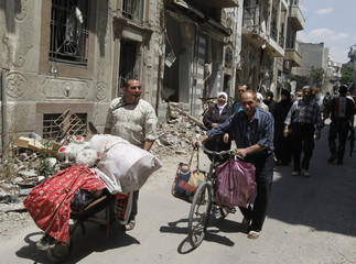 Residents carry belongings from home following the cessation of fighting between rebels and forces loyal to Syria's President Bashar al-Assad, in Homs city