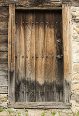 Old rural weathered boards vintage wooden door on stonewall facade