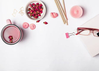 Herbal rose tea and different feminine accessories of pink color