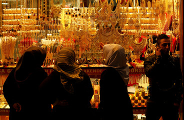 Women look at gold jewelleries at a jewellery shop at the Grand Bazaar in Istanbul