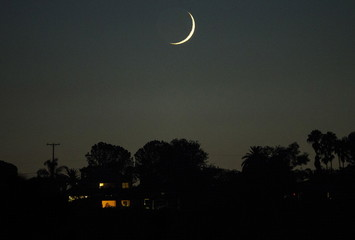 The moon passes over a hillside home as evening turns to night in Encinitas
