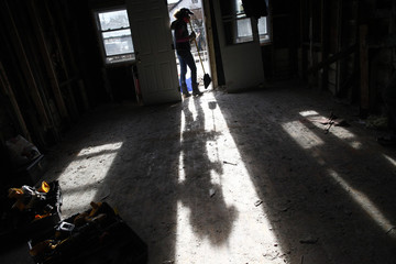 A volunteer carries a broom in a home damaged by Hurricane Sandy in the Staten Island borough of New York