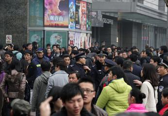 "Police look on as people are told to move along at the corner of the Peace Cinema, after calls for a ""Jasmine Revolution"" protest, organized through the internet, in downtown Shanghai"
