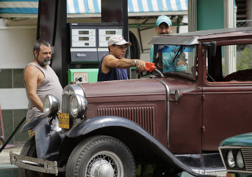 A petrol station worker refuels a U.S.-made 1932 Ford car in Havana