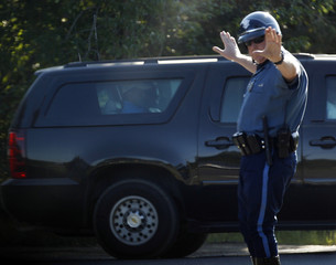 A Massachusetts State police officer stops traffic for a vehicle carrying U.S. President Barack Obama and first lady Michelle Obama on Martha's Vineyard in Edgartown, Massachusetts
