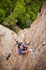 Rock climber scaling boulder crack