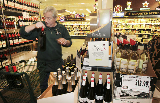 Central Market wine clerk Hedstrom makes shelf space as Washington State retailers prepare to sell liquor on June 1, 2012 as Initiative 1183 takes effect