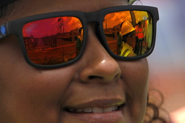 A woman smiles as the new locks are reflected in her sunglasses at the Panama Canal Expansion project on the outskirts of Colon City