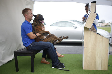 McNaughton smiles as he carries his dog Wayne for a photograph at Milo's Kitchen Treat Truck in San Francisco