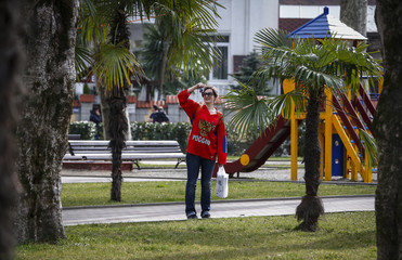 A fan of Russia takes pictures near palm trees on a warm day in Adler during the 2014 Sochi Winter Olympics
