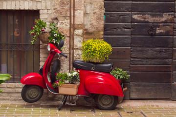 Vespa decorata con vasi di fiori in un vicolo del borgo medievale di Spello