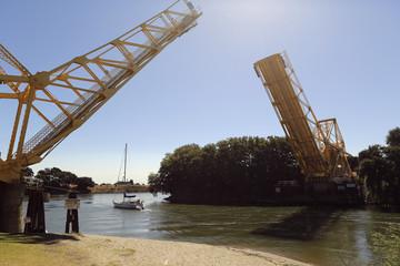 A sailboat cruises beneath a drawn bridge from a slough in the Sacramento San Joaquin River Delta near Walnut Grove, California