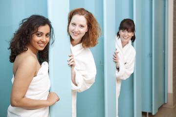 Women standing in shower stalls in locker room