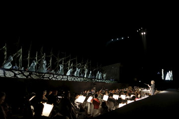 Judd conducts the orchestra as performers are seen on the stage during a dress rehearsal for Carmina Burana at Masada